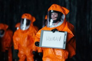 "Amy Adams in a contamination suit holding a sign with word ""Human"""